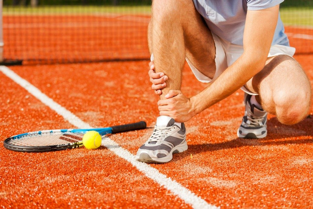 Close-up of tennis player touching his leg while sitting on the tennis court